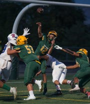 Manogue's Drew Scolari (12) throws against Reno in the first half on Friday night, September 21, 2018 at Bishop Manogue High School in Reno.