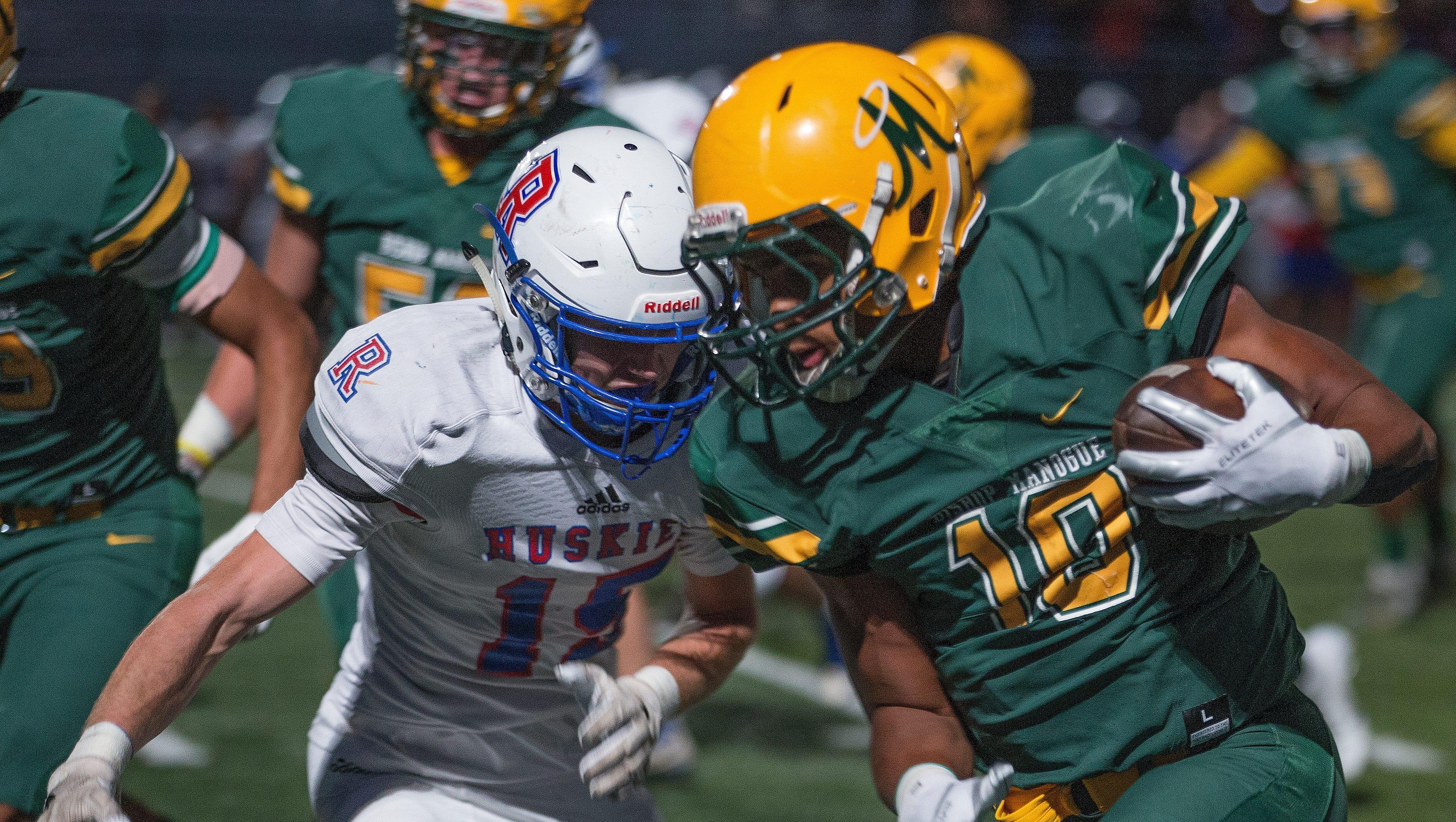 Manogue's Peyton Dixon( 10) is hit by Reno's Taskar Eason(15) in their football game played on Friday night, September 21, 2018 at Bishop Manogue High School in Reno.