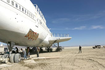 A crew of volunteers work to move a 747 airplane off of the Black Rock Desert playa on Sept. 21, 2018.