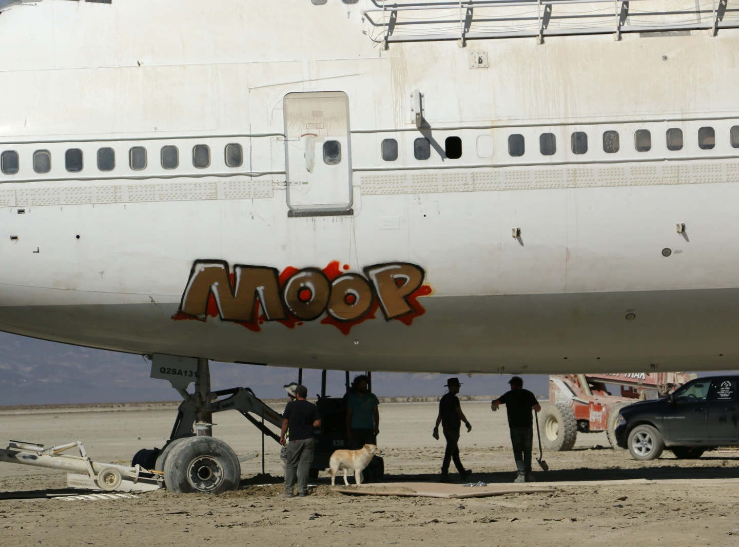 A crew of volunteers work to move a Burning Man art airplane off of the Black Rock Desert playa on Sept. 21, 2018.