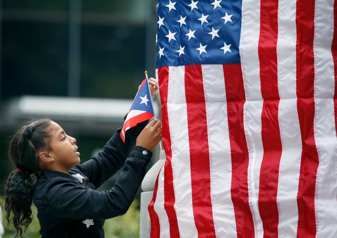 Gabriela Montilla, 11, of Rochester places a Puerto Rican flag next to the American flag for the victims of Hurricane Maria during a vigil at Washington Square Park.