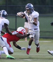 Eastridge quarterback Sher'Ron Davis keeps the ball and cuts back through the line for a gain.
