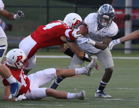 Eastridge running back Matthew Brantley sheds a tackle attempt by Penfield's Chris Barnett.
