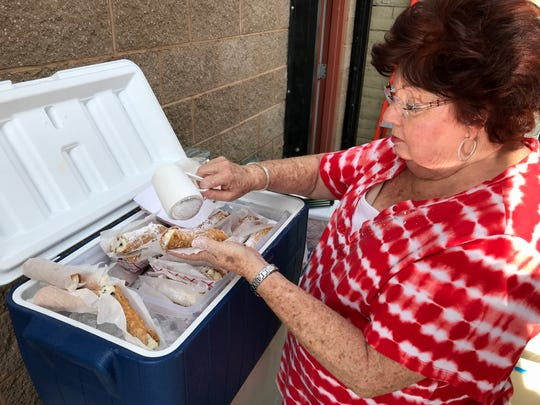 Tina Lamanna of the Sons and Daughters of Italy in America Shasta Lodge No. 2453 sprinkles powdered sugar on cannolis during Saturday's Paesano Days at Tiger Field. Lamanna said the group prepared 500 of the Italian pastries for sale during the festival.