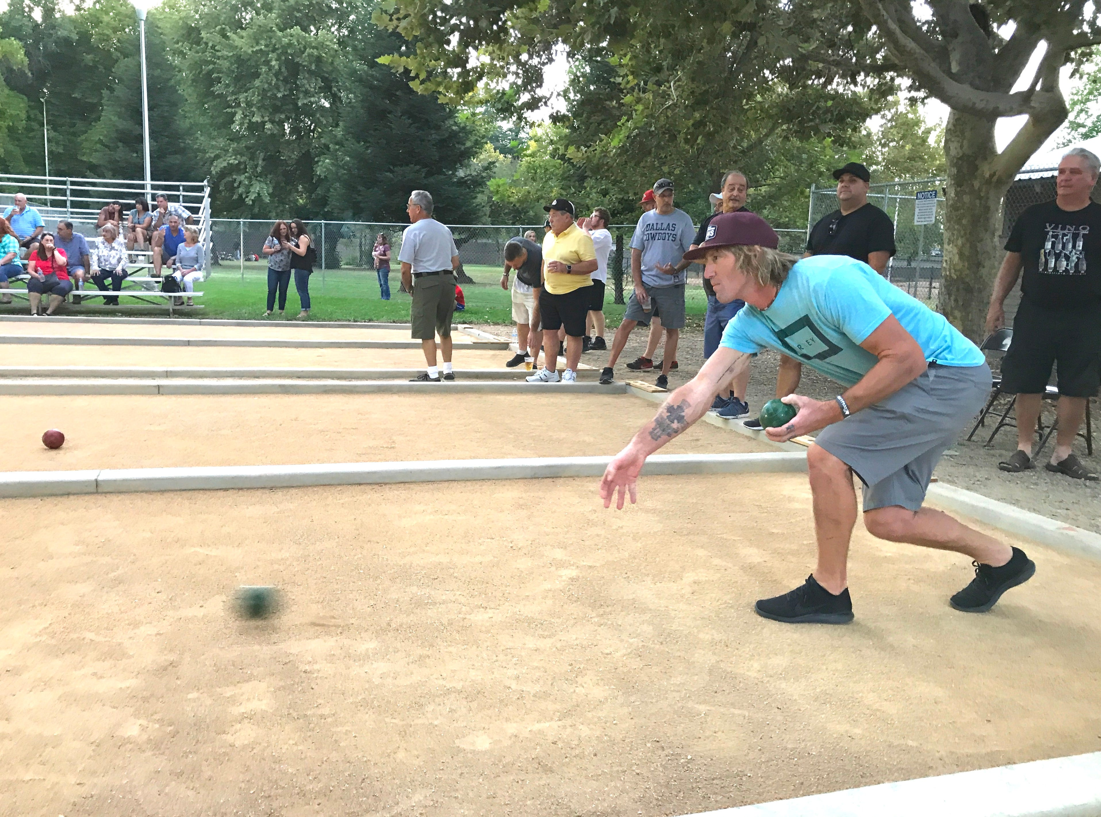 Isaac Archibald of Redding makes a practice roll Friday evening in the two-day bocce ball tournament at South City  Park. Archibald was on the Signsations team