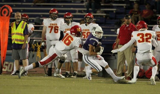 Shasta's Brayden Coon (4) tries to break away from Chico's Kobe Hood (16) and Willy Baker (32) in the 3rd quarter.  Chico won the game, 37-0, at Shasta High on Friday, Sept. 21.