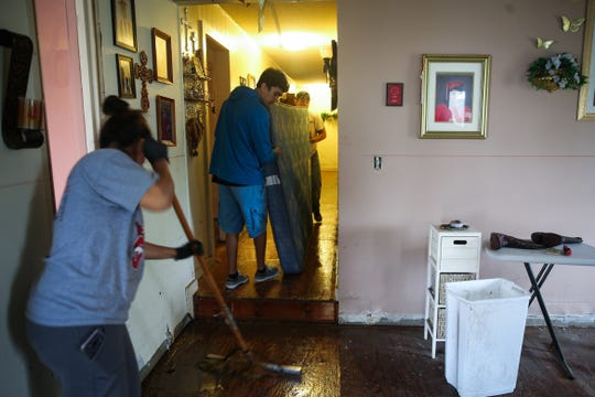 Family and friends help clear carpeting and ruined furniture from Juanita Duran's home Saturday, Sept. 22, 2018, in Sonora. Duran's home and vehicle were damaged during Friday's flood.
