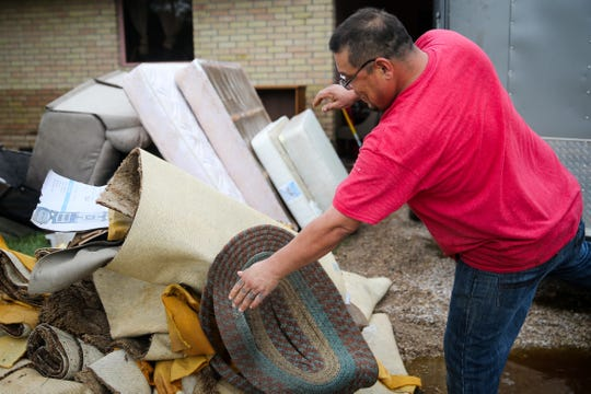 Jamie Arispe removes carpeting from a home damaged by the flood Saturday, Sept. 22, 2018, in Sonora.
