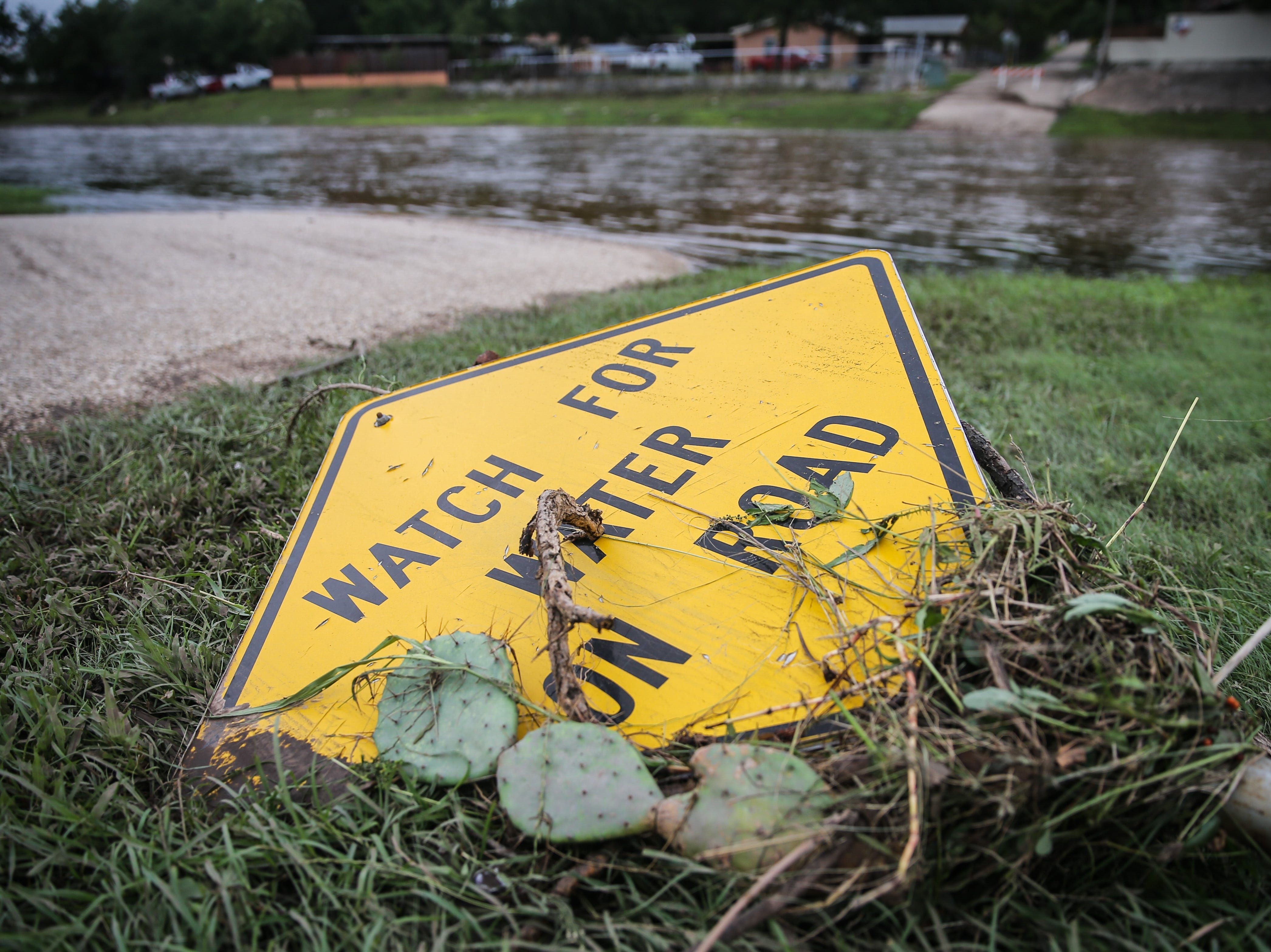A street sign lays on the ground with debris Saturday, Sept. 22, 2018, after rain water flooded the draws Friday afternoon in Sonora.