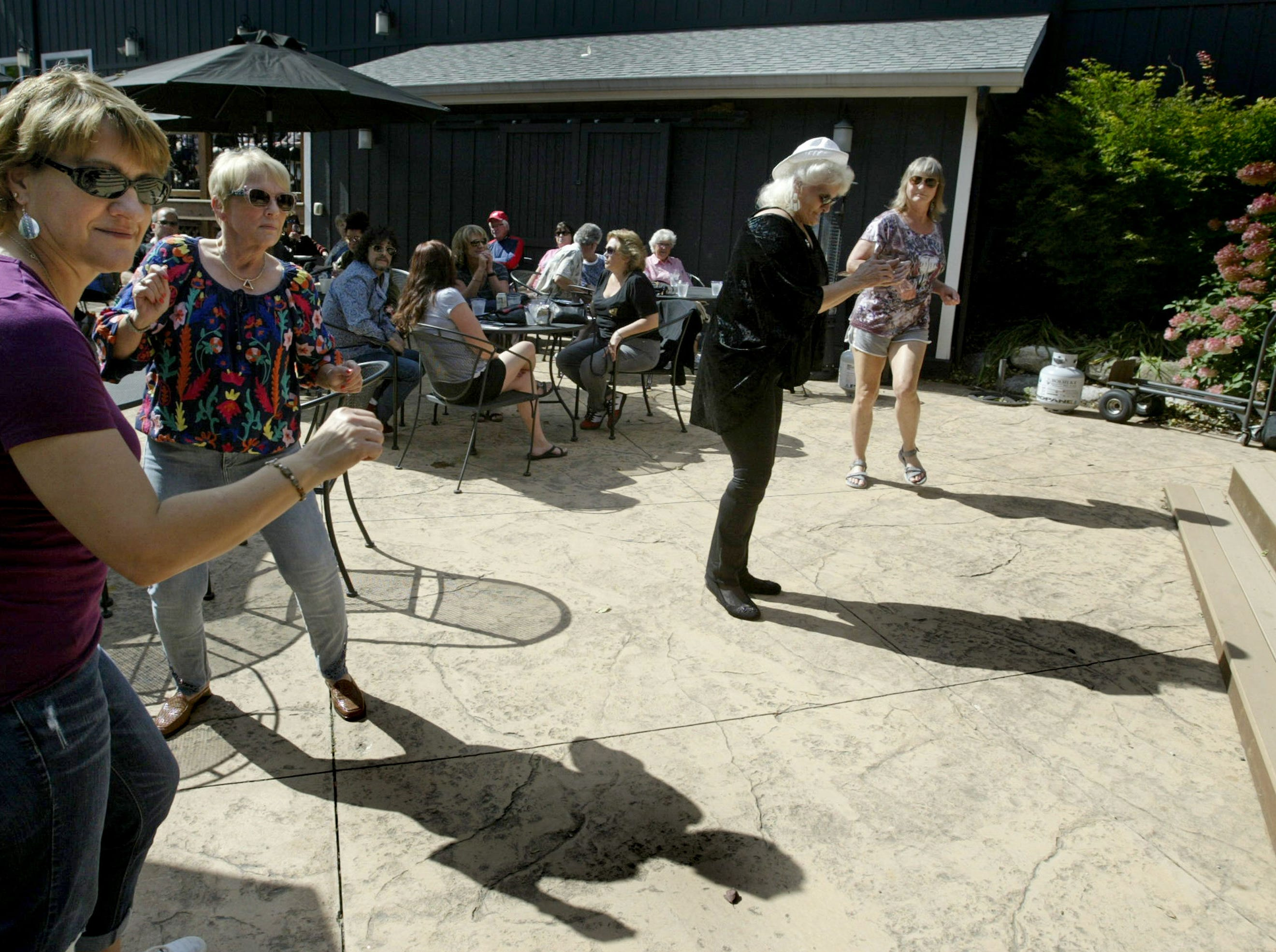 People and their shadows dance to the music of the Beer Belly Idols at the Harvest Festival & Grape Stomp at The Blind Horse Restaurant and Winery, Saturday, September 22, 2018, in Kohler, Wis.