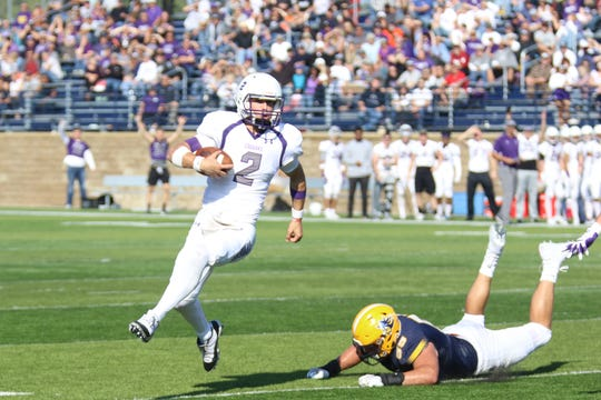 USF quarterback Caden Walters escapes pressure from an Augustana defender during NSIC action last season.