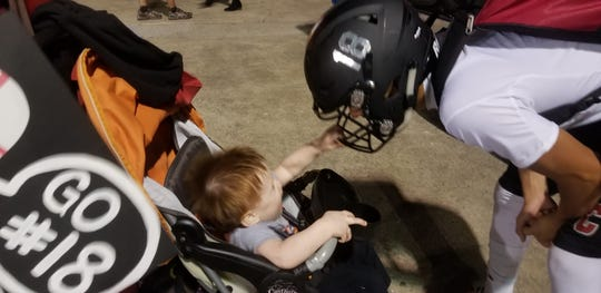 Jimmy Walker (right) lets his son Braylen, 14 months, play with his facemask after Friday night's loss to Waynesville.