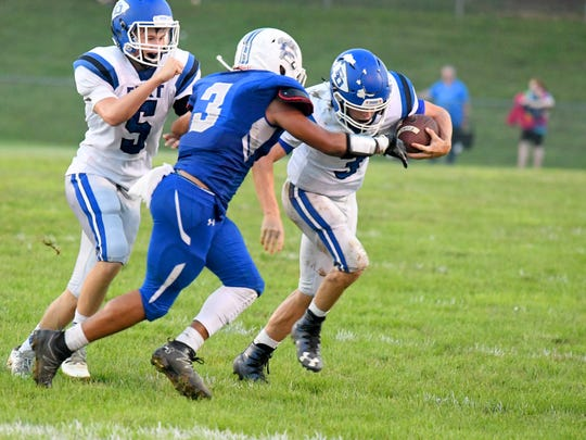 Fort Defiance's Cole Sligh has the ball, trying to break free of a tackle attempt by Rockbridge County's Elijah Poindexter as Fort's Donald Seekford (left) tries to assist during a football game played in Lexington on Friday, Sept. 21, 2018.