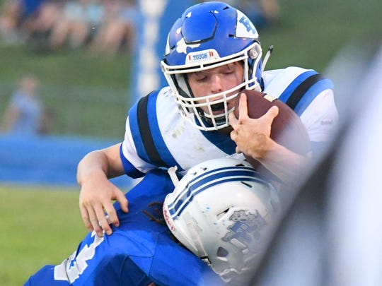 Fort Defiance's Cole Sligh braces himself with the ball as Rockbridge County's Elijah Poindexter shoves him out of bounds during a football game played in Lexington on Friday, Sept. 21, 2018.