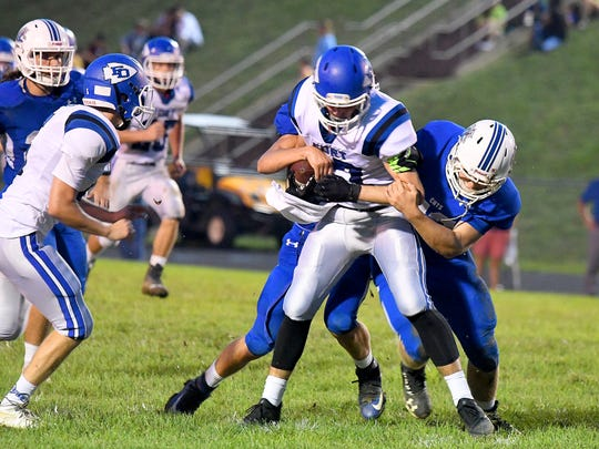 Fort Defiance's Bryce Owens struggle but holds onto the ball as he is wrapped up from behind by two Rockbridge County defenders during a football game played in Lexington on Friday, Sept. 21, 2018.