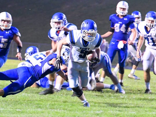 Fort Defiance's Matthew Wonderley slips past Rockbridge County defenders and keeps going with the ball during a football game played in Lexington on Friday, Sept. 21, 2018.
