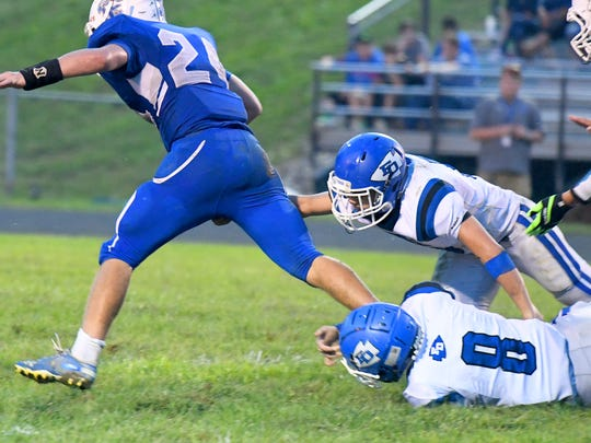 Fort Defiance's Addison Nicely (bottom right) and Colby Morris work together, trying to tackle Rockbridge County's Chase Crook who has the ball during a football game played in Lexington on Friday, Sept. 21, 2018.