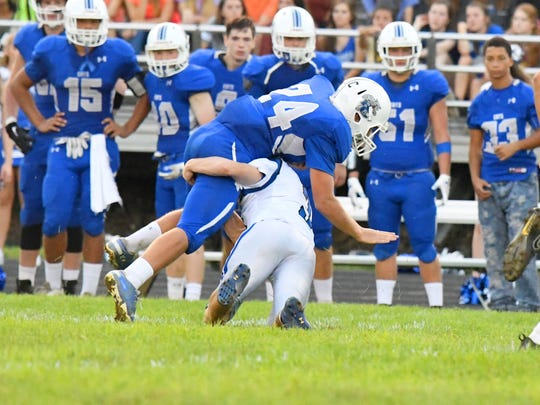 Fort Defiance's Cole Sligh tackles Rockbridge County ball carrier Chase Crook who folds overtop Sligh during a football game played in Lexington on Friday, Sept. 21, 2018.