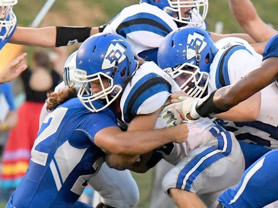 Fort Defiance ball carrier Trevor Bartley (center) is pushed forward by teammate Parker Shenk to keep the forward momentum going for more yards, despite a Rockbridge County's Xavier Shafer (left) trying to make the stop, during a football game played in Lexington on Friday, Sept. 21, 2018.
