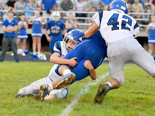 Fort Defiance's Cole Sligh (left) grabs the Rockbridge County's Chase Crook, who has the ball, around the legs as teammate Dalton Ream gets in on the tackle during a football game played in Lexington on Friday, Sept. 21, 2018.