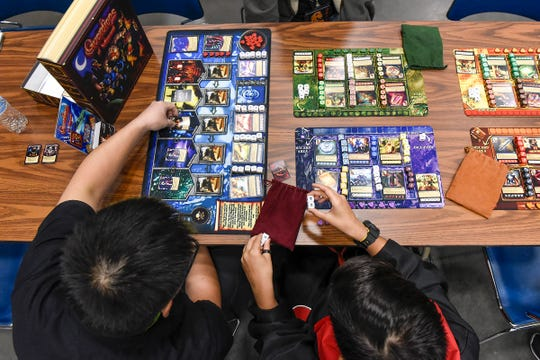 Ethan Chaudhary, 13, learned to play the board game Guardians of Wayword with Ben Pohl of Kid Loves Tiger Games in Milaca during LionCon on Saturday.
