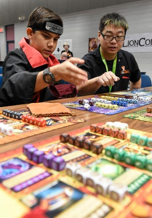 Ethan Chaudhary, 13, learned to play the board game Guardians of Wayword with Ben Pohl, of Kid Loves Tiger Games in Milaca, during LionCon on Saturday at the River's Edge Convention Center.