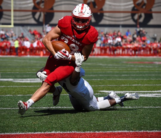 St. John's tight end Tommy Auger breaks a Carleton tackle and goes in to score in the first half Saturday, Sept. 22, in Collegeville.