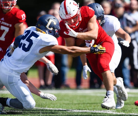 St. John's running back Adam Essler crosses the line to score on a short run against Carleton in the first half Saturday, Sept. 22, in Collegeville.