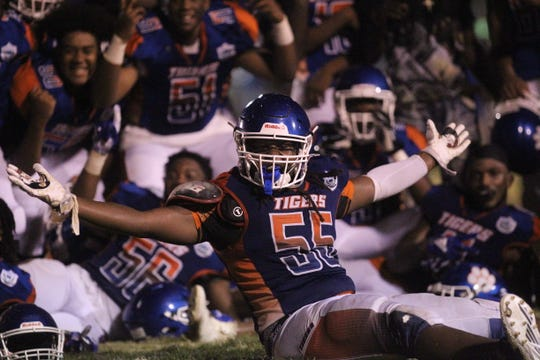 Jefferson County's Kimiri Thomas (55) leads a celebration after the Tigers beat FAMU DRS 25-22 on Sept. 21, 2018.