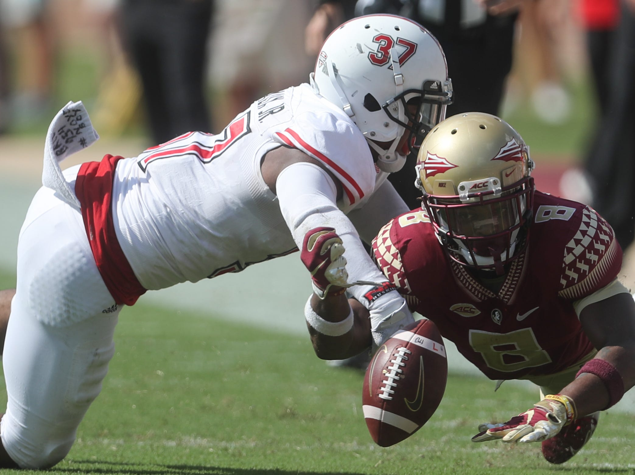 Florida State Seminoles wide receiver Nyqwan Murray (8) loses the ball as Northern Illinois Huskies linebacker Lance Deveaux Jr. (37) tackles him during a game between the Florida State University Seminoles and the Northern Illinois University Huskies at Doak S. Campbell Stadium in Tallahassee, Fla. Saturday, September 22, 2018.