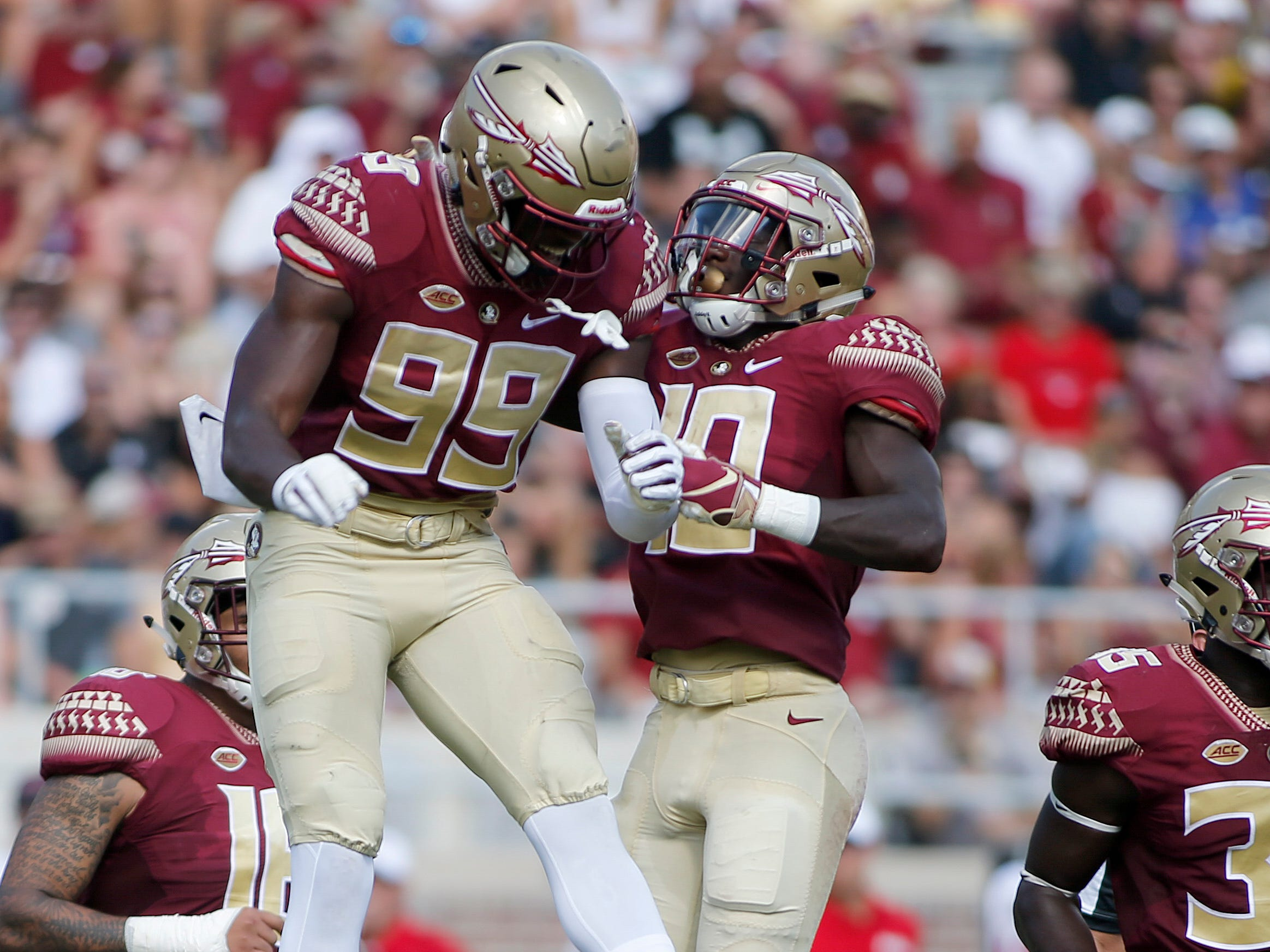 Sep 22, 2018; Tallahassee, FL, USA; Florida State Seminoles defensive end Brian Burns (99) and defensive back Calvin Brewton (10) celebrate during the second quarter of play at Doak Campbell Stadium.