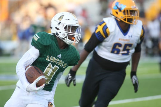 Lincoln safety Jalen Glaze looks upfield on the way to a 35-yard interception return touchdown as the Trojans displayed new white helmets while beating Rickards' 49-0 Friday at Gene Cox Stadium.