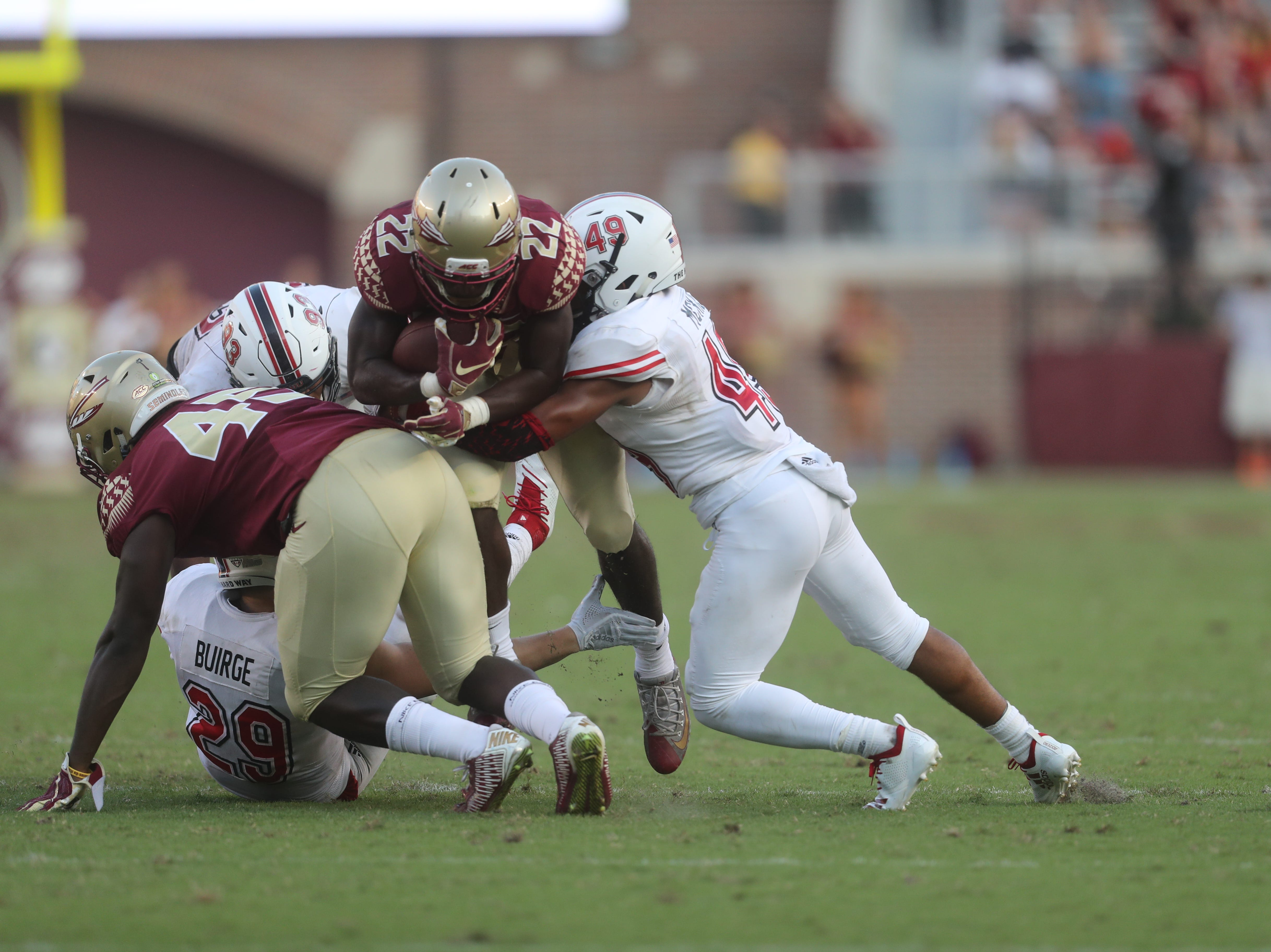 Florida State Seminoles running back Amir Rasul (22) gets tackled by a pack of Huskies during a game between the Florida State University Seminoles and the Northern Illinois University Huskies at Doak S. Campbell Stadium in Tallahassee, Fla. Saturday, September 22, 2018.