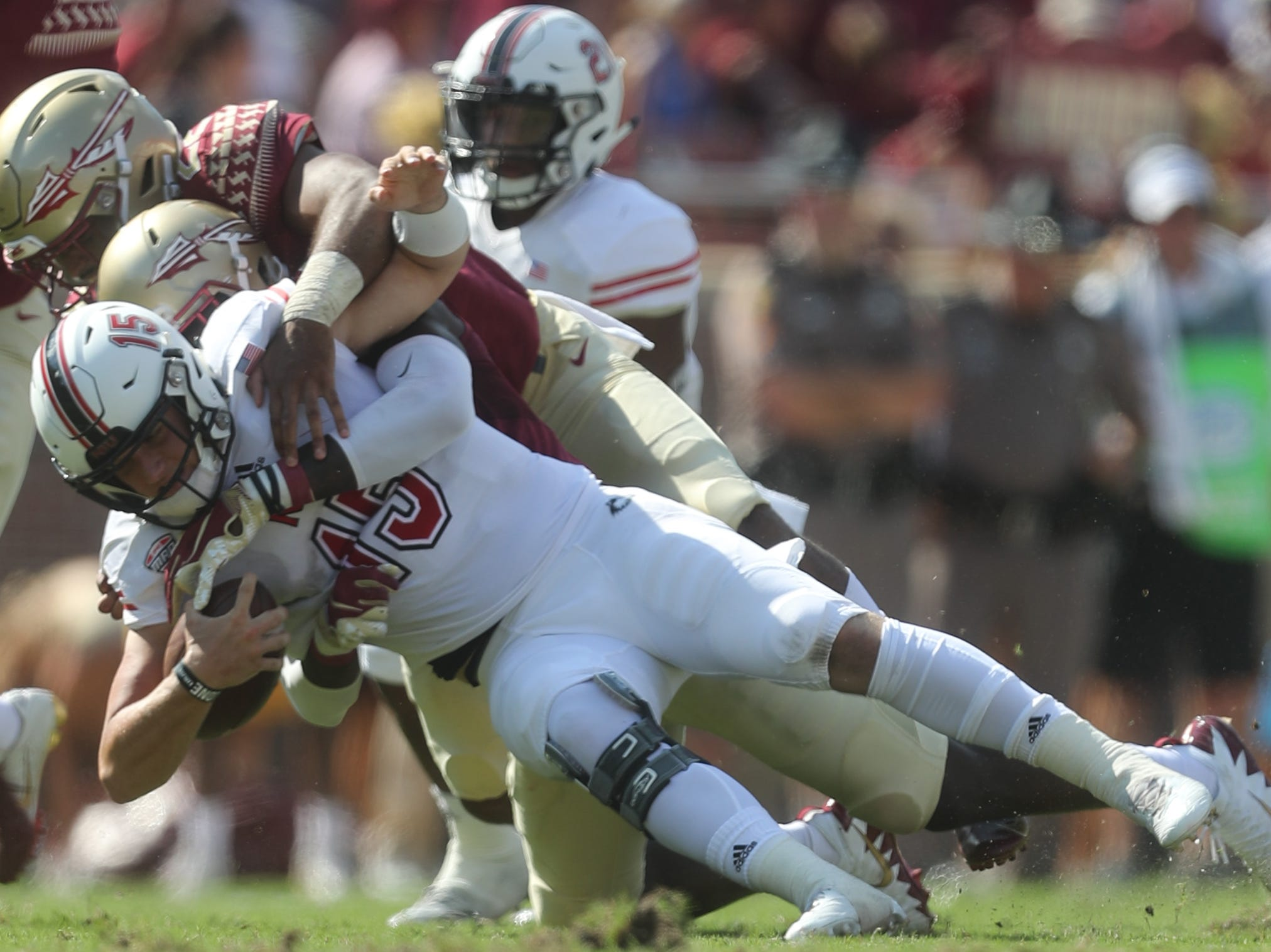 Northern Illinois Huskies quarterback Marcus Childers (15) is brought down by a pair of Seminoles during a game between the Florida State University Seminoles and the Northern Illinois University Huskies at Doak S. Campbell Stadium in Tallahassee, Fla. Saturday, September 22, 2018.