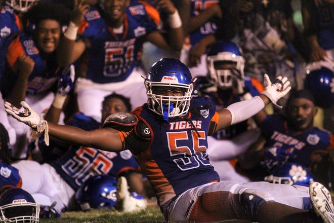 Jefferson County's Kimari Thomas celebrates with his teammates after the Tigers beat FAMU DRS 25-22 on Friday night.