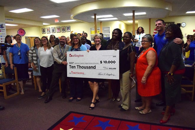 Faculty and staff of Apalachee Elementary and the Leon County Schools stand with a check for $10,000 for classroom supplies from Burlington Clothing and AdoptAClassroom.org.