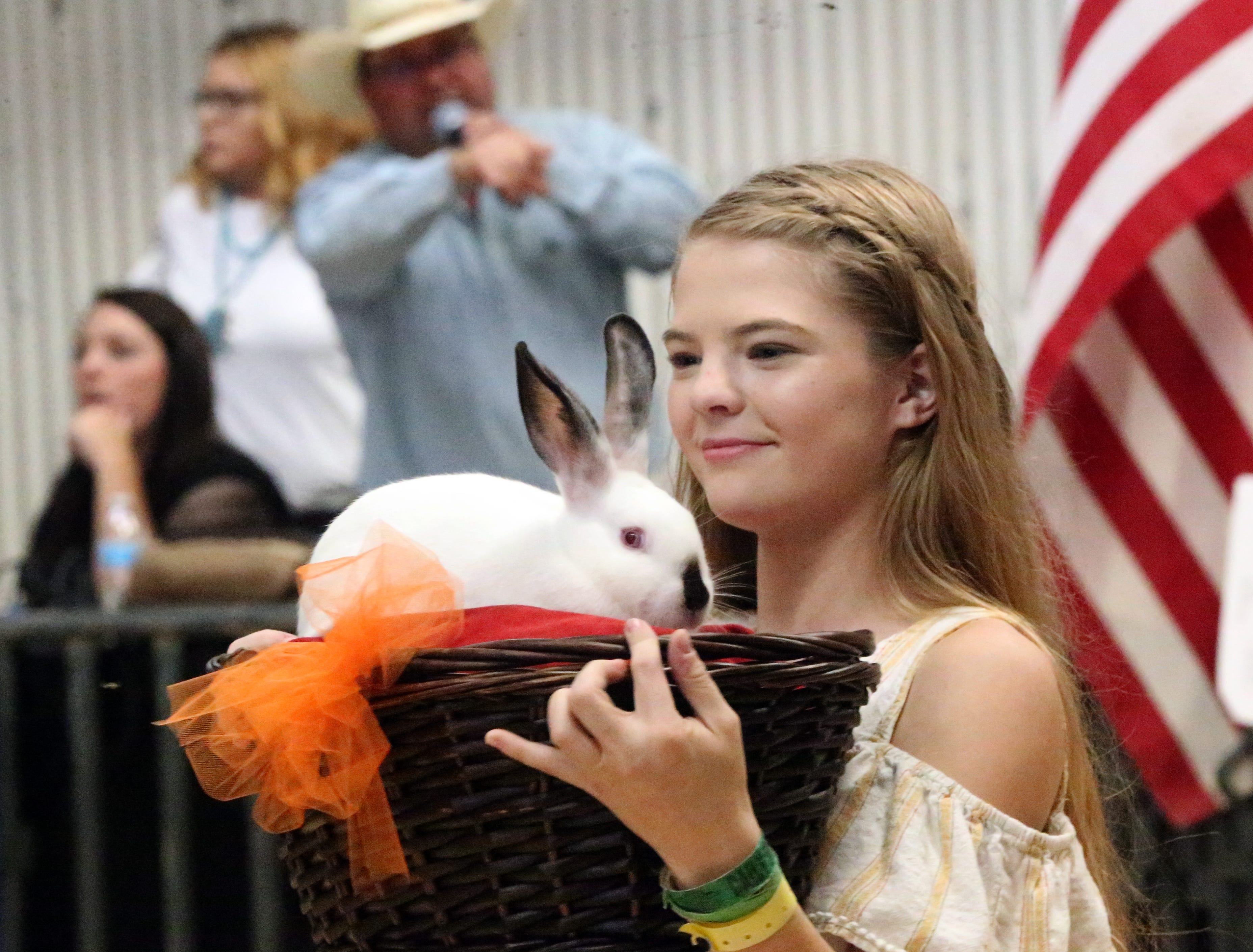Shelby Gillette of Doña Ana, N.M., shows her grand champion California rabbit during the El Paso County Fair & Junior Livestock Show auction Saturday in the El Paso County Judging Arena behind the County Coliseum. The animal auctioned for $1,100. A variety of animals, including market steers, market hogs, market lambs and goats, as well as poultry and waterfowl, were auctioned off from young people from El Paso, Hudspeth, Culberson and Doña Ana counties, said Jeep Darnell of the El Paso County Fair Association. The fair and auction have been held for over 50 years, Darnell said.