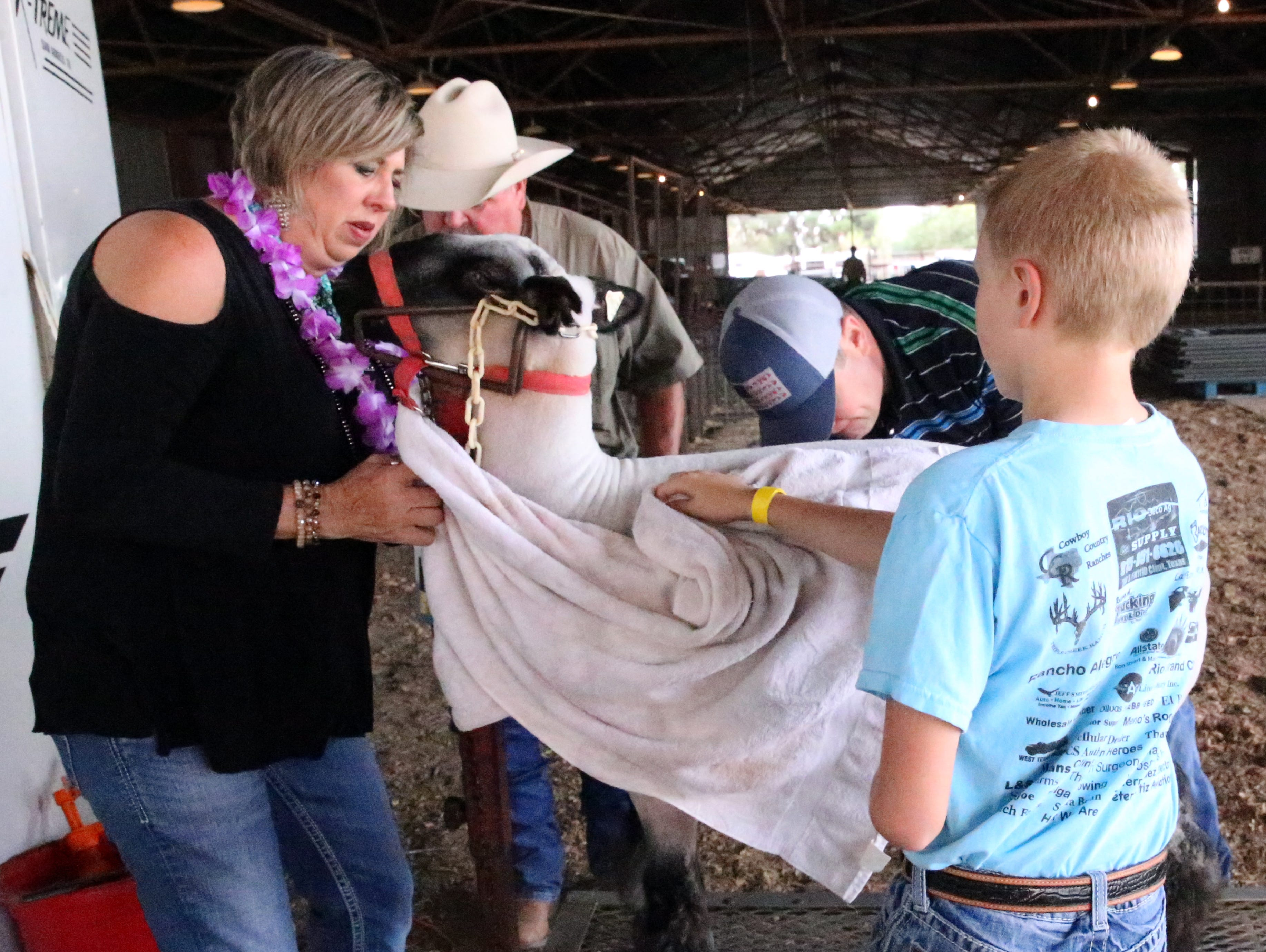 Shandra Giraud, left, of Clint, helps children prepare a market lamb for auction Saturday.