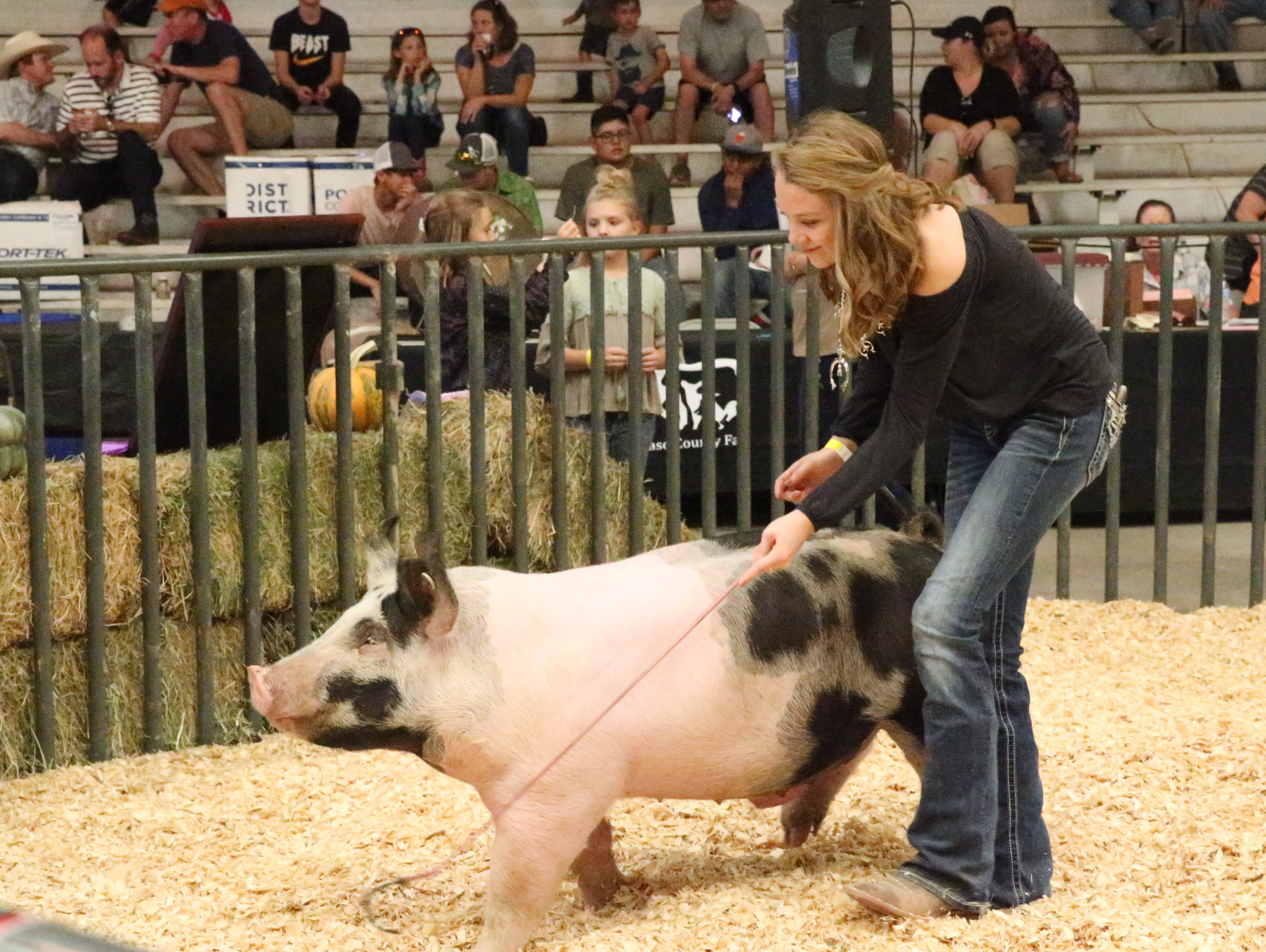 Kaelyn Darden of Las Cruces shows her Reserve Grand Champion hog during Saturday's auction.