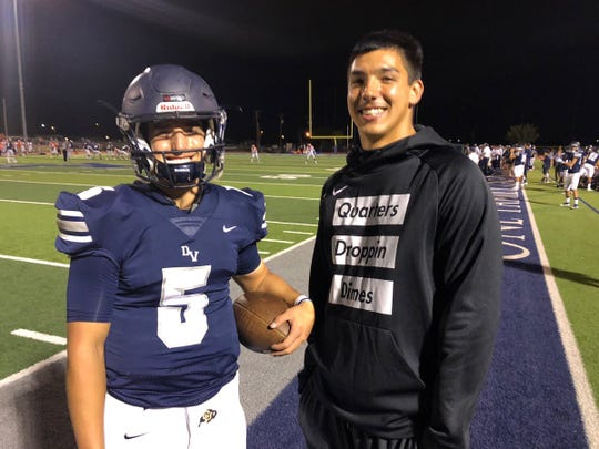 Del Valle quarterback Raymond Montez stands on the sidelines with his big brother, Steven Montez, a Del Valle graduate and former high school quarterback who now starts for the University of Colorado Buffaloes.