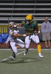 Moorpark High's Joaquin Sandoval uses a stiff-arm to try to shake free of Simi Valley's Hilton Pham during the first quarter of Friday night's game. The Musketeers won 59-21.