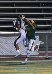 Simi Valley High's Malik Hunt makes a touchdown catch while being defended by Moorpark's Ethan Gomez during the third quarter of Friday night's game. Moorpark won, 59-21.