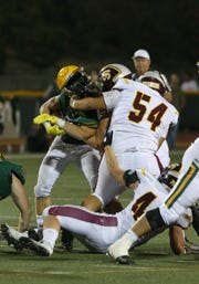 Moorpark High running back Alec Powell looses his helmet while getting hit by Simi Valley's Anthony Carias during the second quarter of Friday night's game.