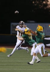 Simi Valley High quarterback Jack Applegate just gets his pass off as he gets hit by Moorpark's Jett Alldredge during the first quarter of the Friday night's game. Moorpark won 59-21.