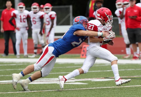 North Rockland's Nick Fenner (27) tries to break away from Carmel's Sam Duke (24) during football action at Carmel High School Sept. 22, 2018. Carmel won the game 27-0.