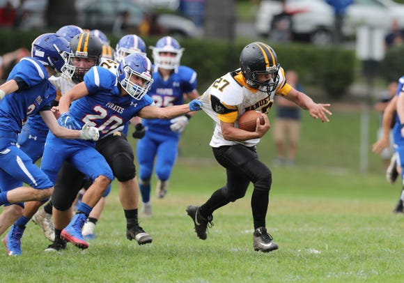 Nanuet's Michael Franchino (27) breaks a tackle during their 14-6 win over Pearl River to claim the Little Brown Jug at MacCalman Field in Nyack on Saturday, September 22, 2018.
