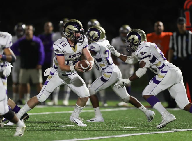 Clarkstown North quarterback hands off to Dupree Darden (21) during their 49-22 win over Spring Valley at Spring Valley High School on Friday, September 21, 2018.