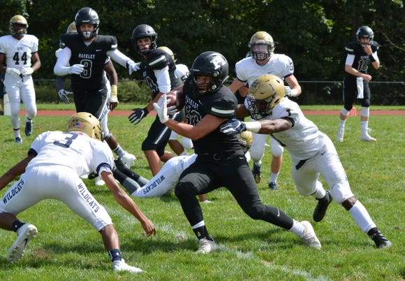 Hackley running back DeWaun Burns is corralled by RCDS defensive backs Allan Houston III (1) and Ben Pearce (3).