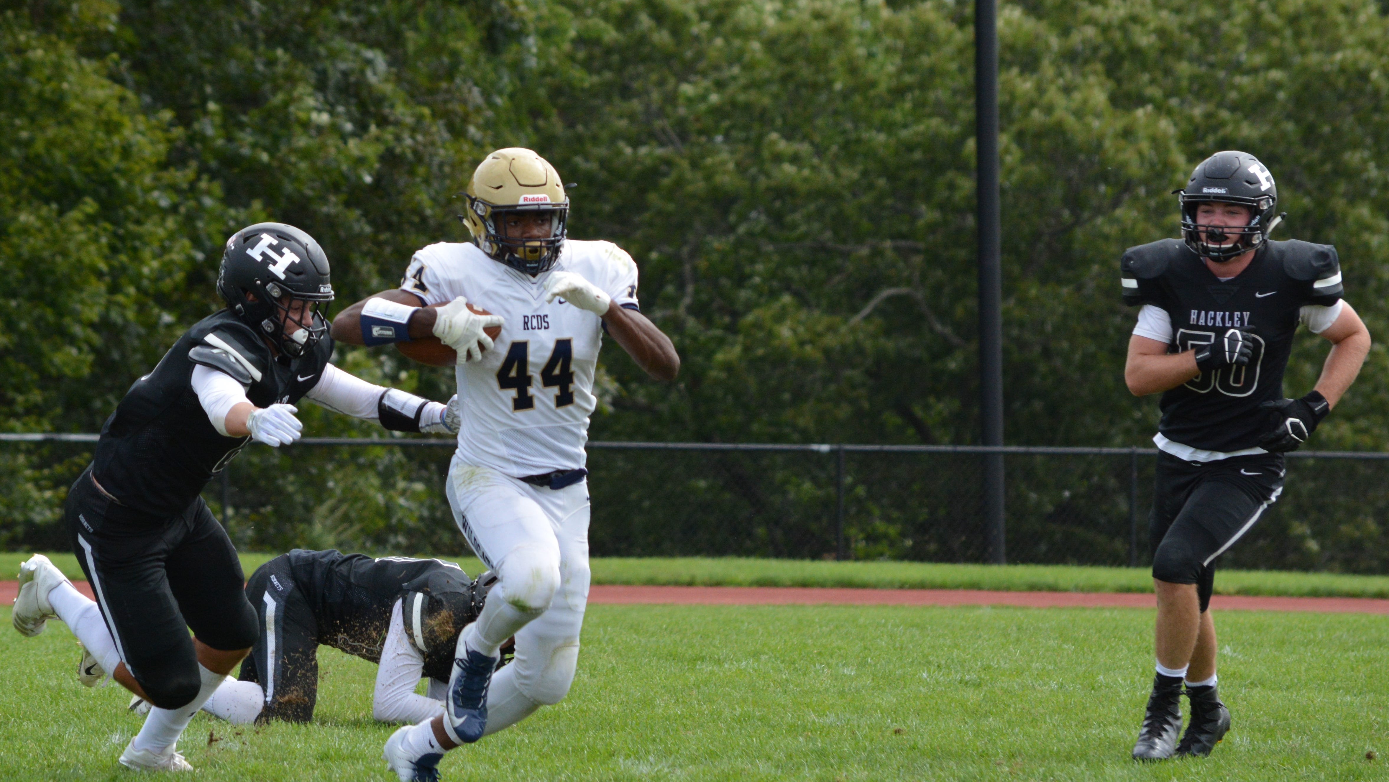 RCDS running back Cullen Coleman avoids the outstretched arms of Hackley defensive back Walter Myers on Saturday.