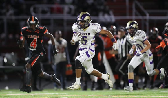 Clarkstown North's Moiz Kamzi (5) finds an opening for a 64-yard run during their 49-22 win over Spring Valley at Spring Valley High School on Friday, September 21, 2018.